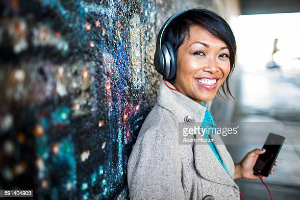 woman listening to cell phone by mural - oakland california stock pictures, royalty-free photos & images