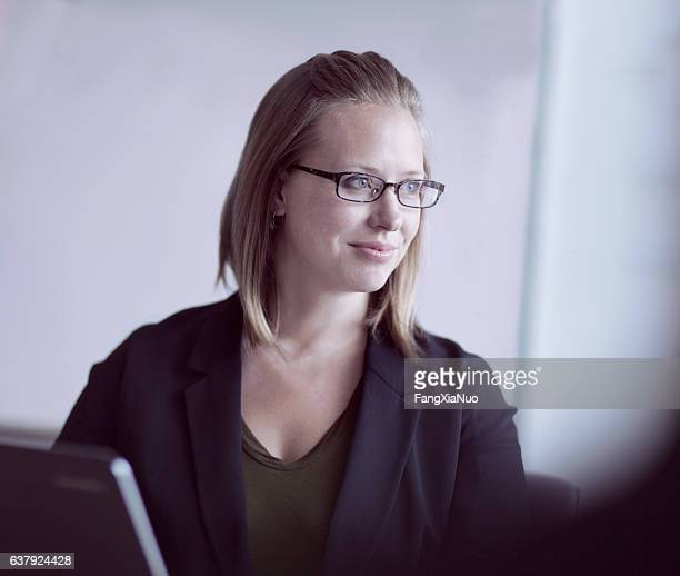 Woman listening to colleagues in office meeting