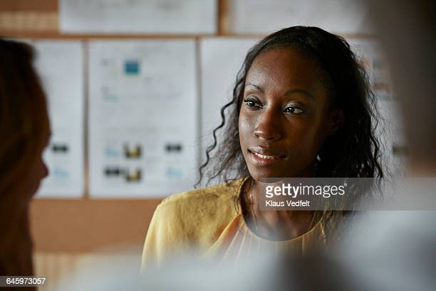 woman listening to co-worker at meeting - leanincollection stock pictures, royalty-free photos & images