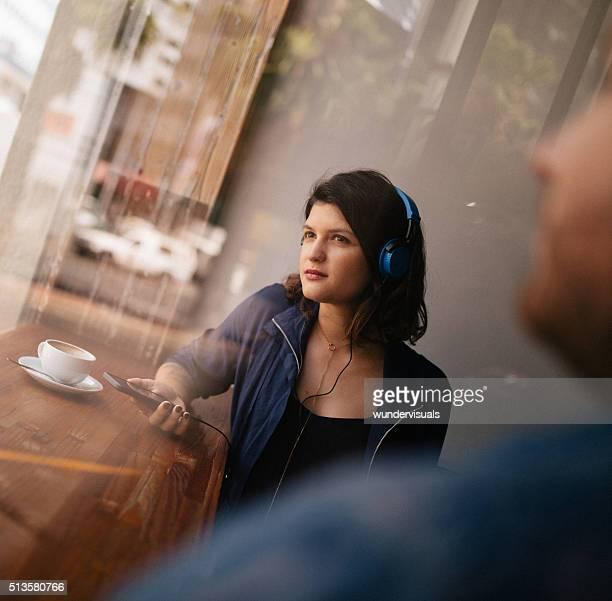 Mulher Ouvindo auscultadores no banco no café janela
