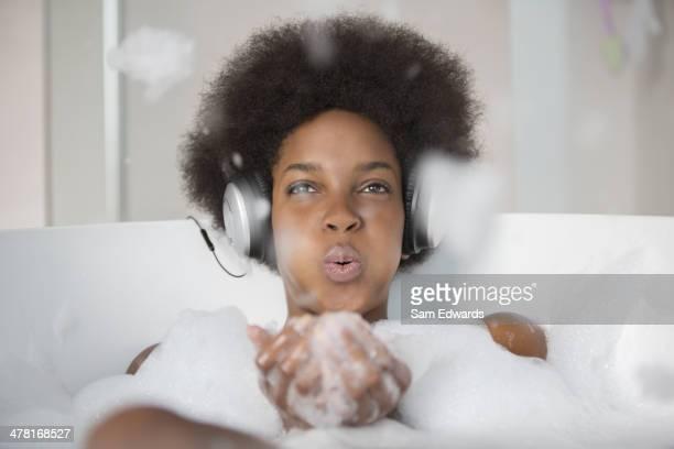 Woman listening to headphones in bath