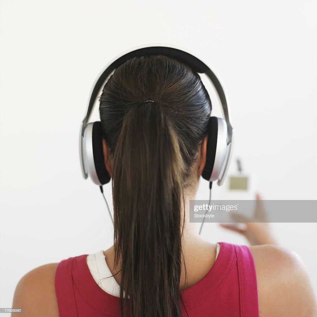 Woman listening to headphones, indoors : Stock Photo