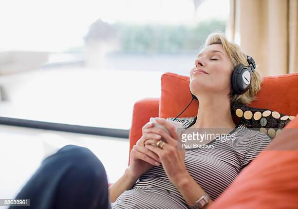 Woman listening to headphones on sofa