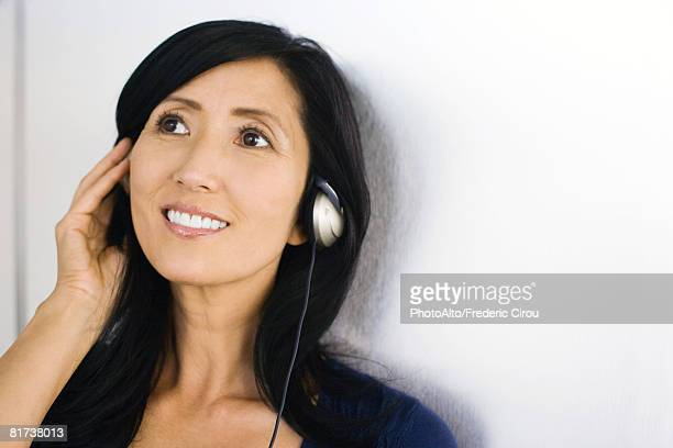 Woman listening to headphones, smiling