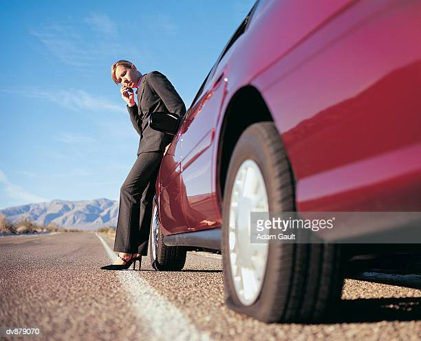 Woman Listening to Her Cellphone Next to Her Broken Down Car