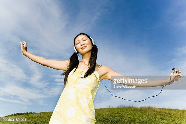 woman listening to mp3 player - chinese music stock pictures, royalty-free photos & images