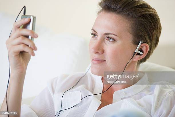 woman listening to mp3 player - mid adult women stock pictures, royalty-free photos & images