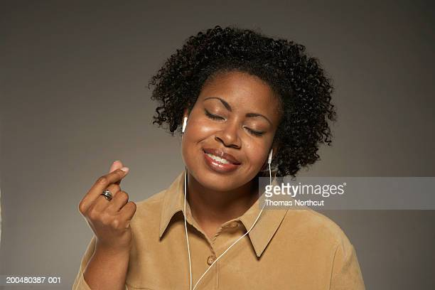 Woman listening to MP3 player, snapping fingers, eyes closed