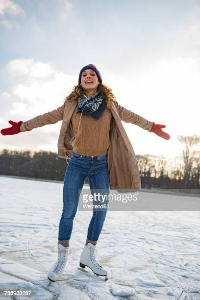 Woman listening to music and ice skating on frozen lake