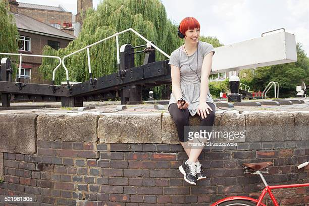 Woman listening to music by canal, East London, UK