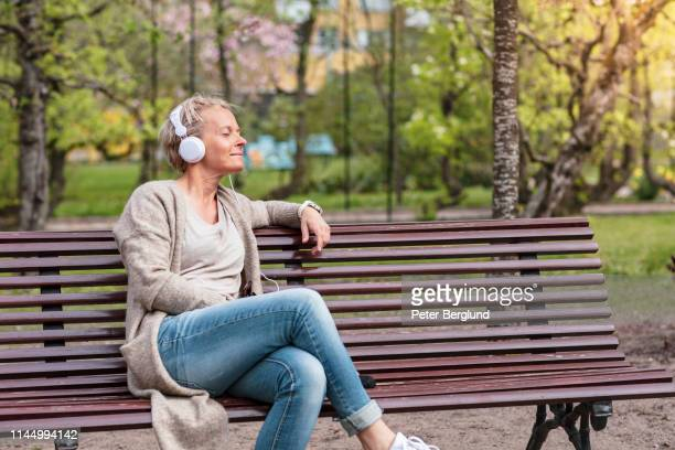 woman listening to music in a park - springtime stock pictures, royalty-free photos & images