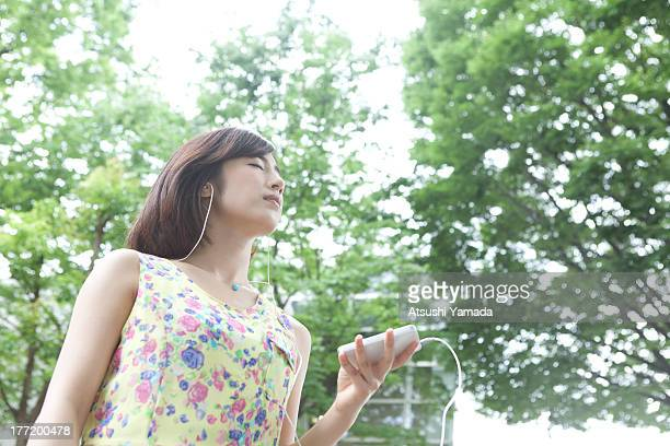 Woman listening to music in forest,closing eyes