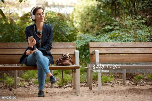 woman listening to music on bench in park - bench stock pictures, royalty-free photos & images