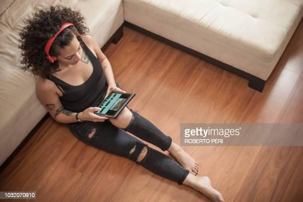 woman listening to music on digital tablet at home - roberto ricciuti foto e immagini stock