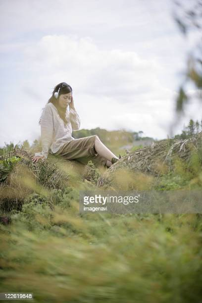 A woman listening to music on the grass