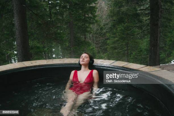 Woman listening to music on wireless headphones in hot tub