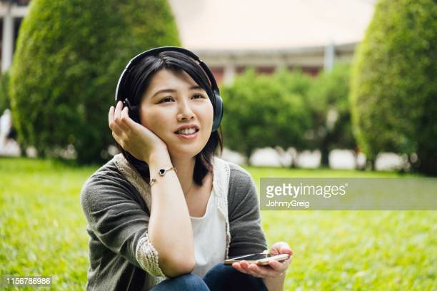 woman listening to music on wireless headphones - east asian ethnicity stock pictures, royalty-free photos & images