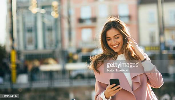 woman listening to music outdoors - bluetooth stock pictures, royalty-free photos & images