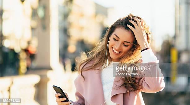 女性の音楽を聞きながら屋外 - 髪に手をやる ストックフォトと画像