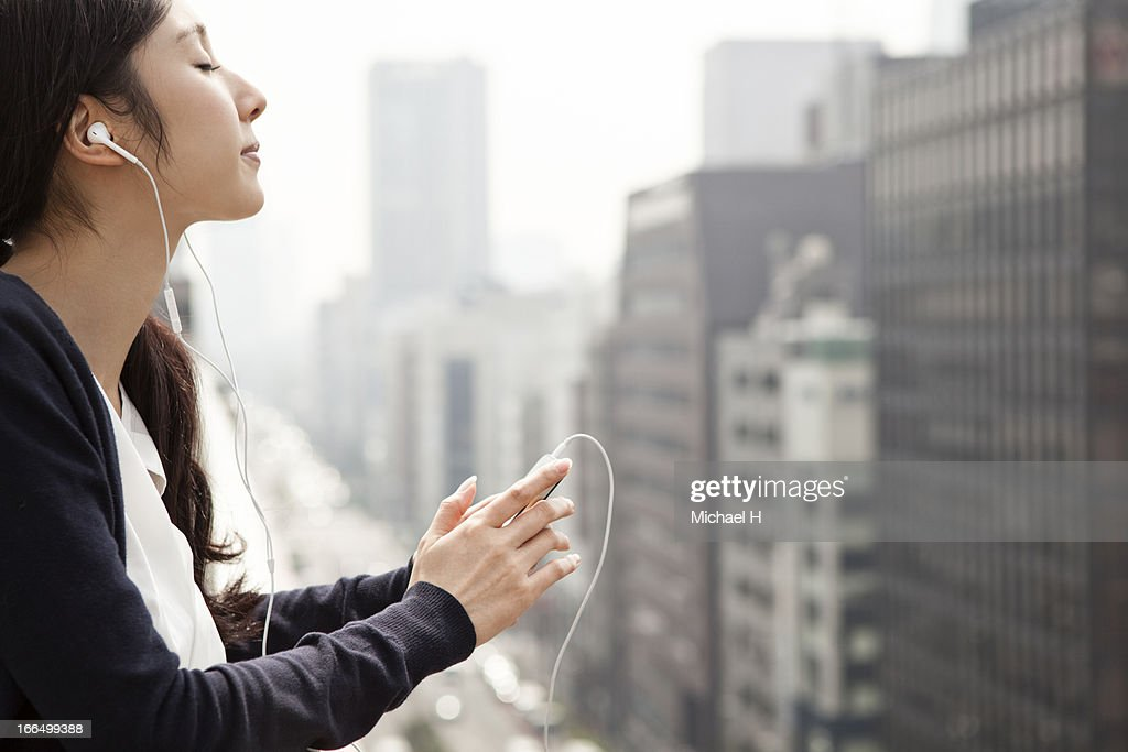 woman listening to music outside by smart phone : Stock Photo