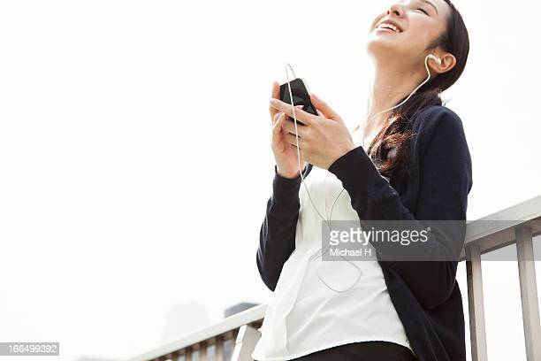 woman listening to music outside by smart phone