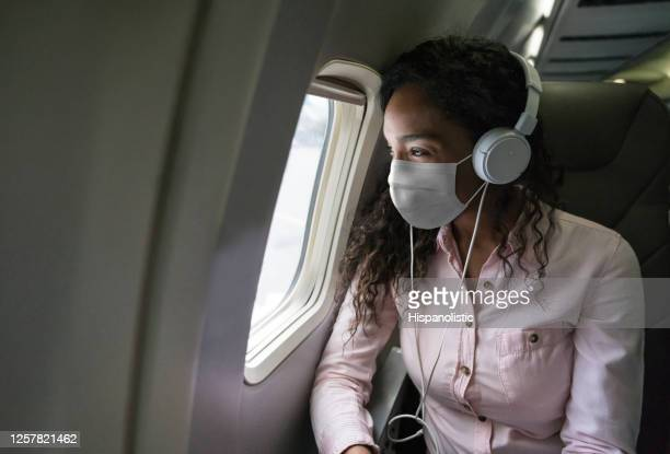 woman listening to music while flying on an airplane wearing a facemask - mid air stock pictures, royalty-free photos & images