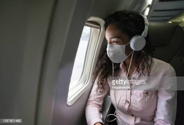 vrouw die aan muziek luistert terwijl het vliegen op een vliegtuig dat een facemask draagt - vliegtuig stockfoto's en -beelden