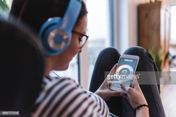 woman listening to music with headphones and smartphone at home - sinal de percentagem imagens e fotografias de stock