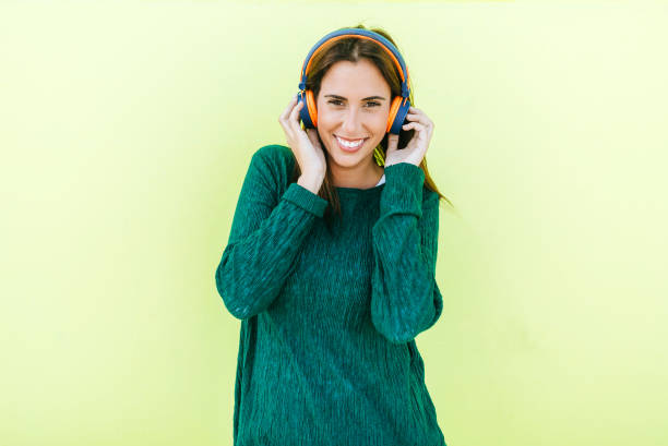 Woman listening to music with headphones in front of green wall