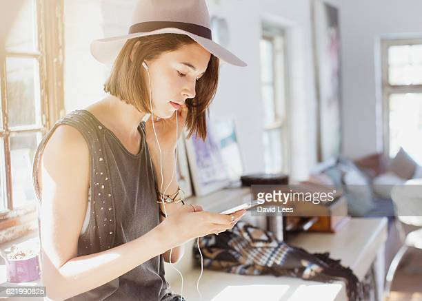 Woman listening to music with headphones indoors
