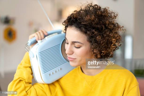 woman listening to music with portable radio at home - radio stock-fotos und bilder