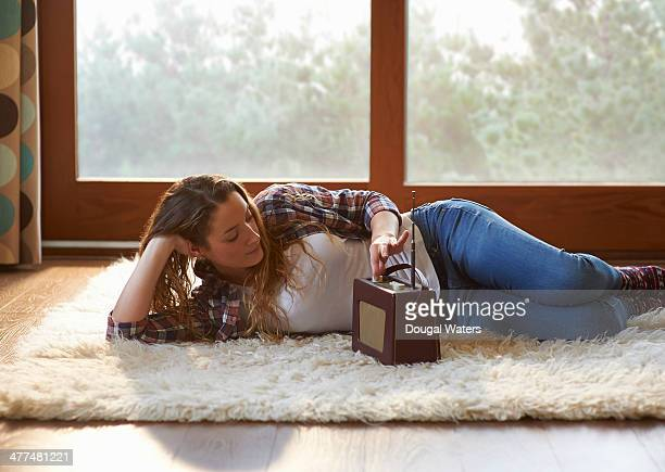 Woman listening to old radio in lounge.