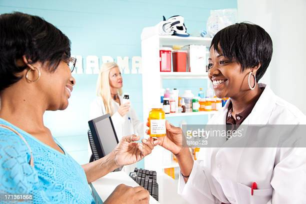 Woman listening to pharmacist about prescription medications