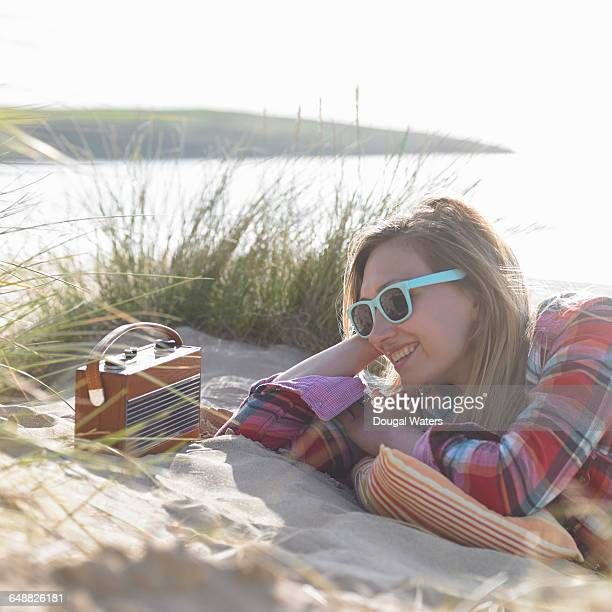 Woman listening to radio at beach.
