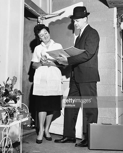 Woman listening to salesman in doorway