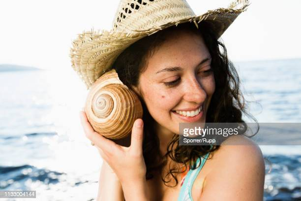 woman listening to seashell on beach - coquillage photos et images de collection