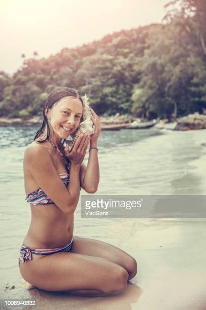 Woman listening to seashell