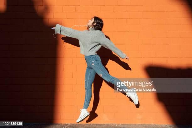 woman listening to the music and jump - gettata foto e immagini stock