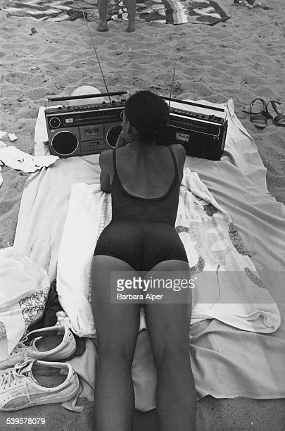 A woman listening to the radio on the beach in New York City 2nd August 1980