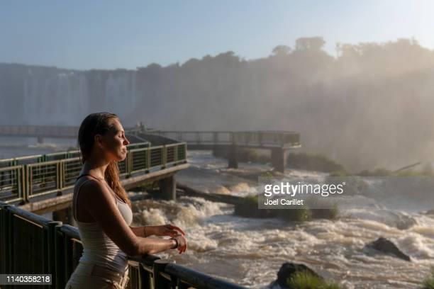イグアスの滝の轟音を聞く女性 - イグアス滝 ストックフォトと画像