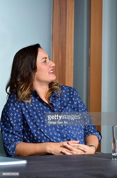 woman listens in a business meeting - rafael ben ari stockfoto's en -beelden