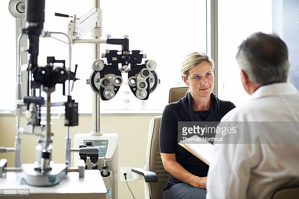 a woman listens to her opthamologist - optometry stock pictures, royalty-free photos & images