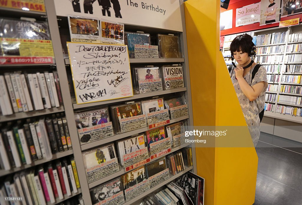 A woman listens to Japanese pop music (J-Pop) at a Tower Records Japan Inc. store in Tokyo, Japan, on Monday, July 1, 2013. Music sales in the country rose for the first time in five years, led by tunes delivered on CDs and other physical media, bucking the trend in developed markets as cheaper downloads gain ground. Physical media made up 82 percent of Japanese music sales last year, versus 37 percent in the U.S., said the Recording Industry Association of Japan. Photographer: Yuriko Nakao/Bloomberg via Getty Images