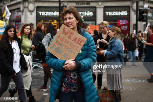 A woman listens to songs as members and supporters of climate change activist group Extinction Rebellion demonstrate at Oxford Circus in London...
