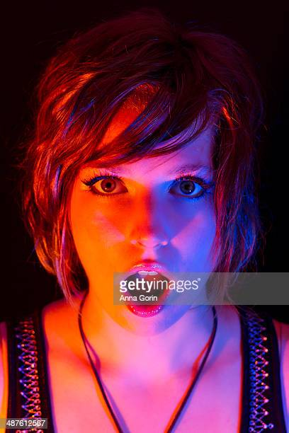 woman lit with colored lights opens mouth in shock - gel effect lighting stock photos and pictures
