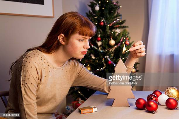 Woman liths candle in front of christmas tree.