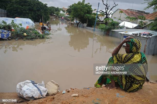 TOPSHOT A woman living at a camp for the internally displaced sits on high ground above a flooded street on May 20 2018 in Mogadishu after temporary...