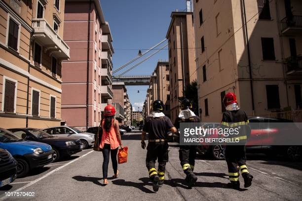 A woman living near the Morandi motorway bridge is escorted by firefighters during his evacuation two days after a section collapsed in Genoa on...