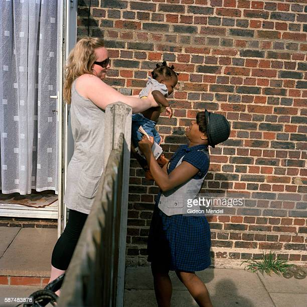 A woman living on the Kingsmead Estate passes her young baby over the garden fence to her neighbor who is a good friend The estate has 980 flats and...