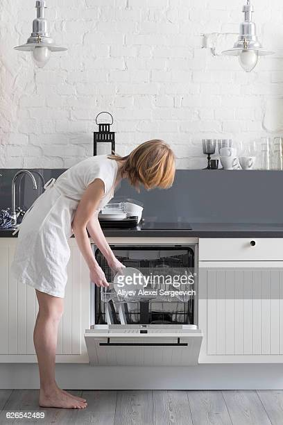 Woman loading dishes into dishwasher